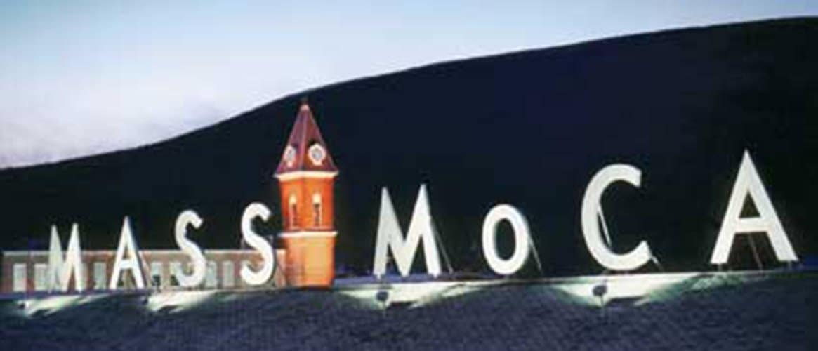 MASS MoCA sign lit up at night with a hill silhouetted in the background.