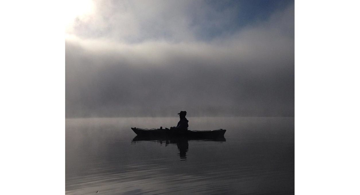 Kayaker silhouette on a lake with fog rising in the Berkshires near Porches Inn.