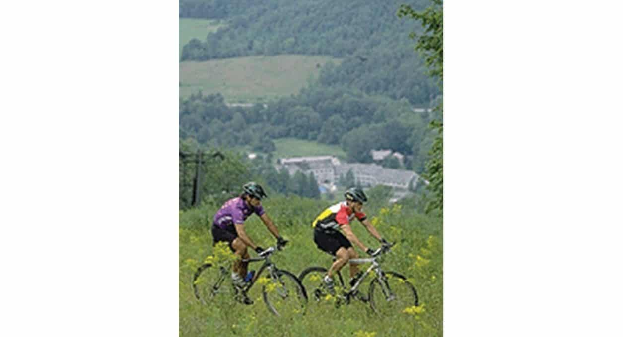 Two mountain bikers riding on a trail near Porches Inn.