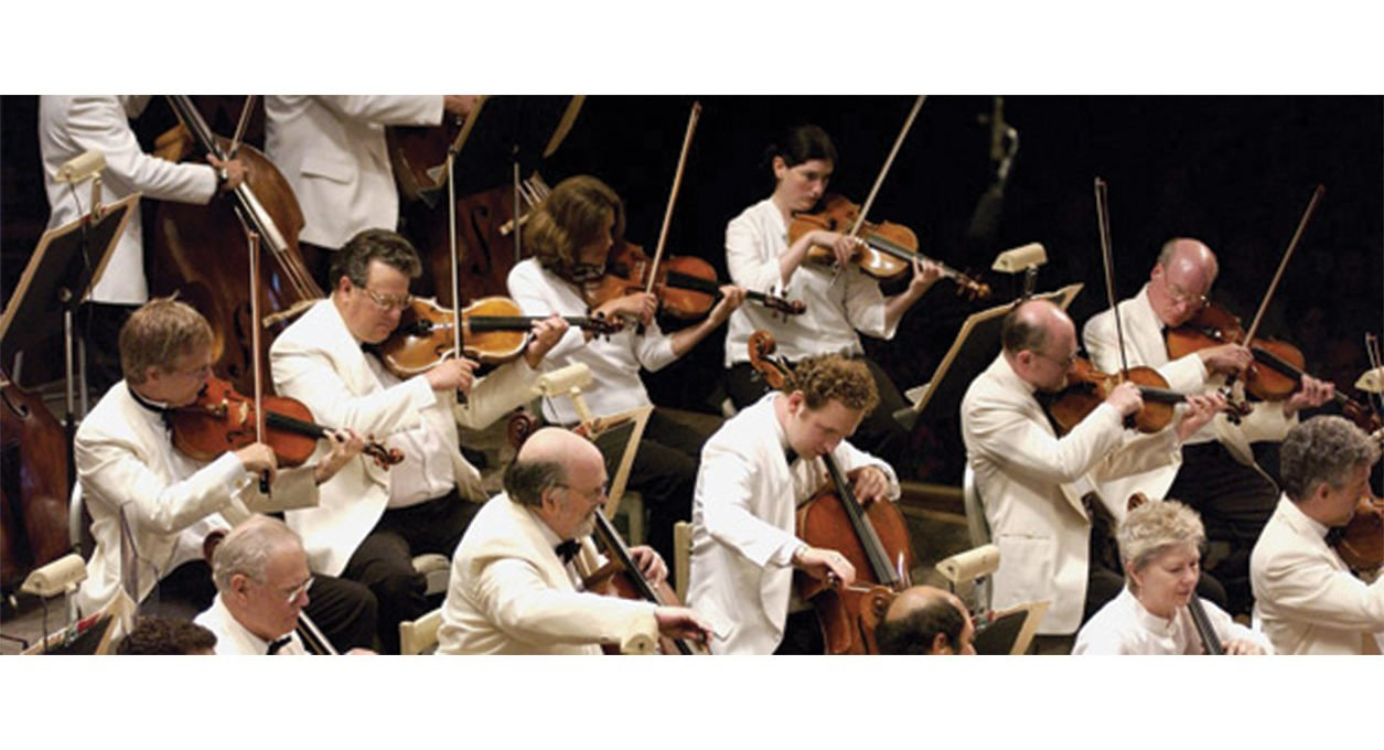 Orchestra performing on stage dressed up in white tuxedos.