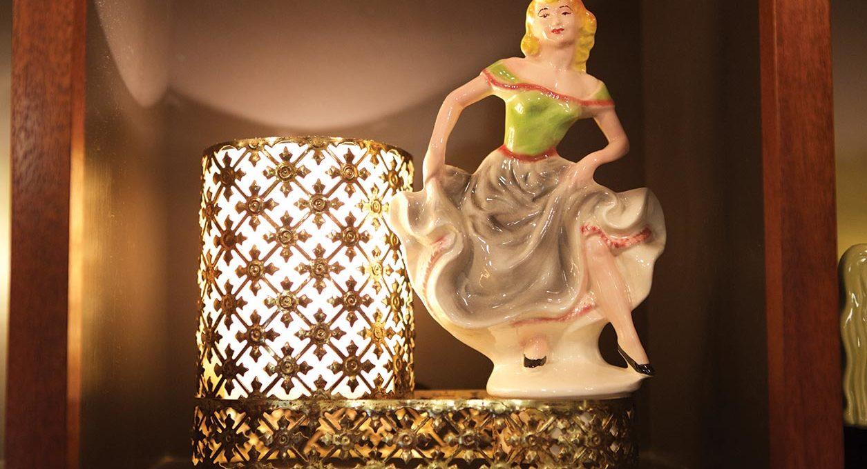Candle with a ceramic figurine of a woman dancing.