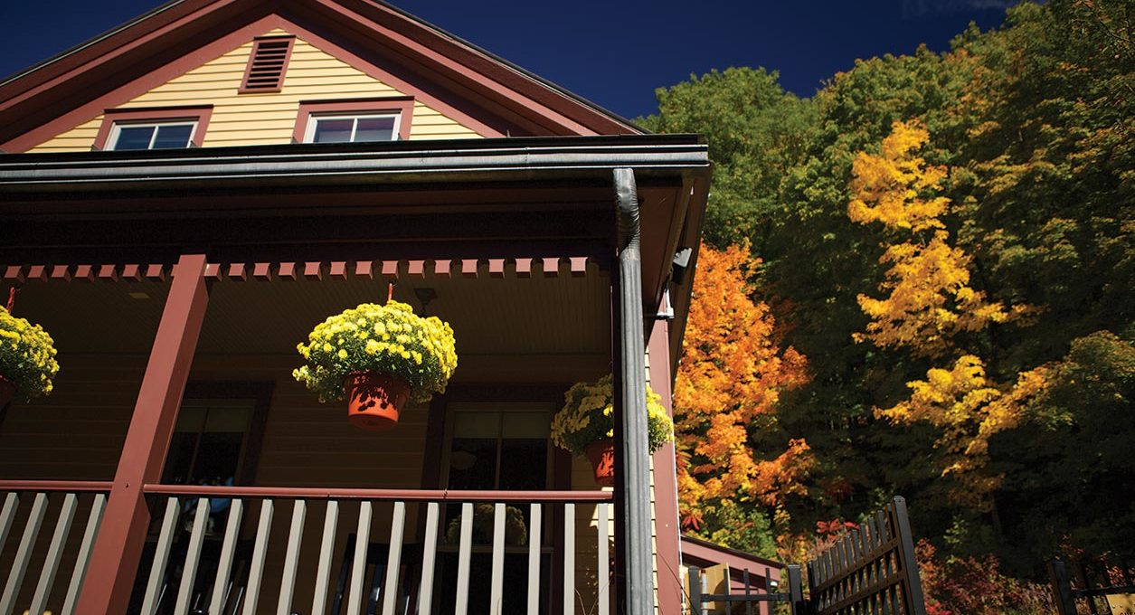 Porches Inn façade with hanging plants and fall trees changing colors in the background.
