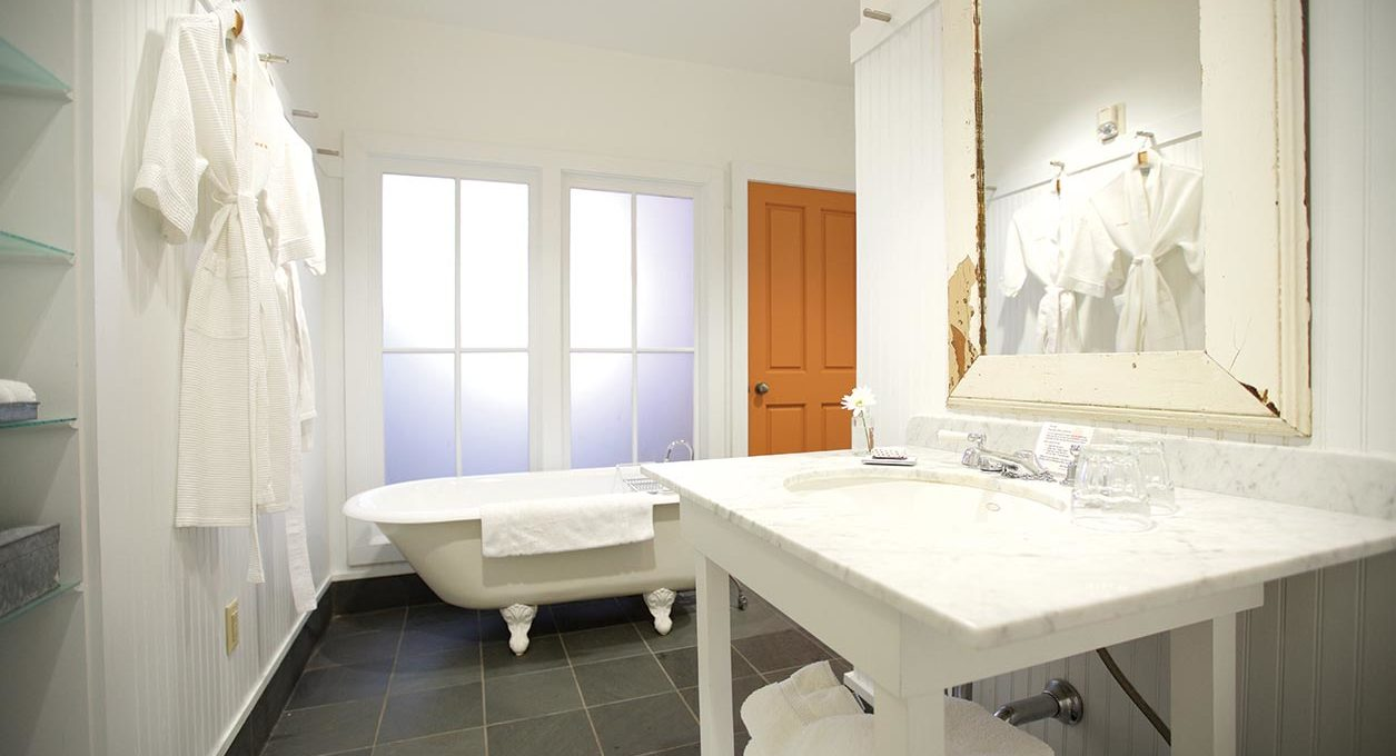 Sleek white bathroom with a large bathtub and white furnishings at Porches Inn.