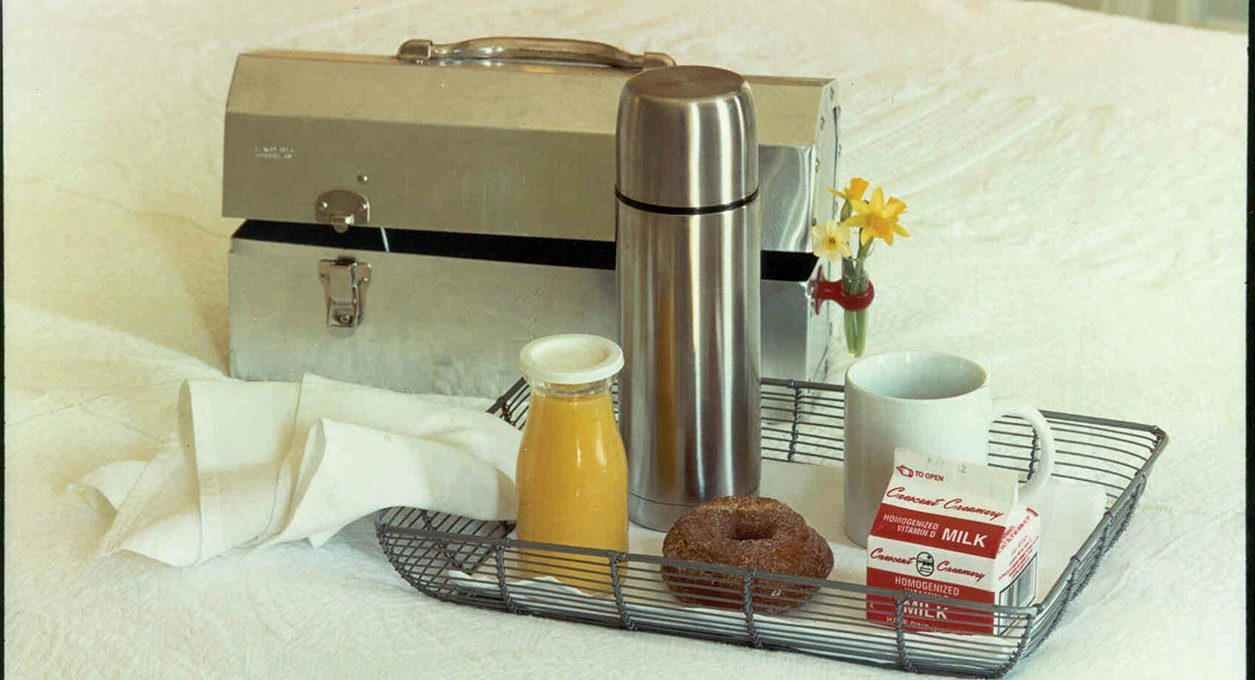 Metal wired breakfast tray in bed with a metal toolbox with a small bouquet of flowers attached on the side.