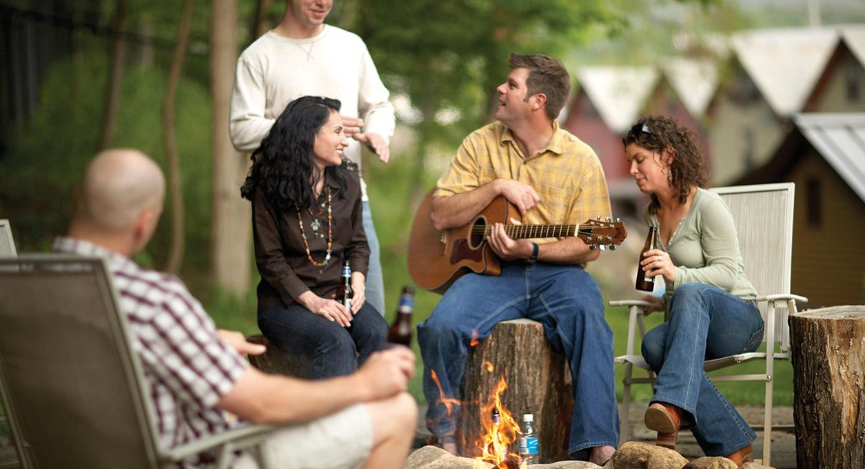 Guests with a guitar and beers relax near the fire at our hotel near mass moca