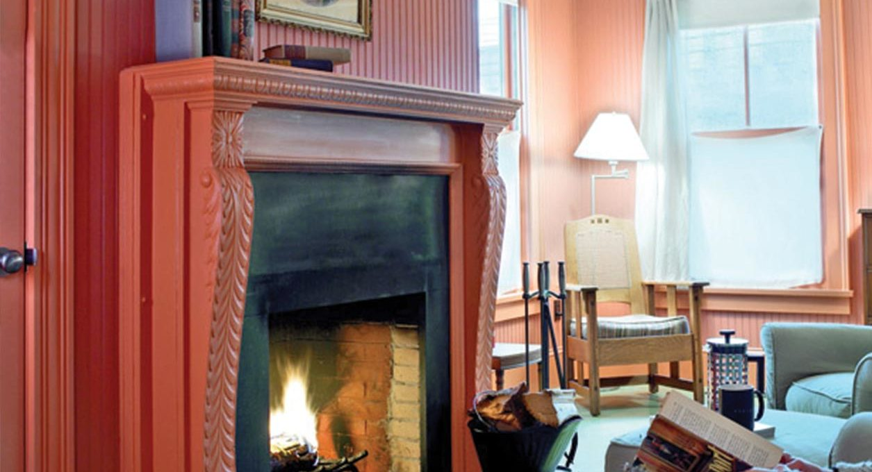 Room with a fireplace and pink walls with a guest reading and drinking coffee in the background at Porches Inn.