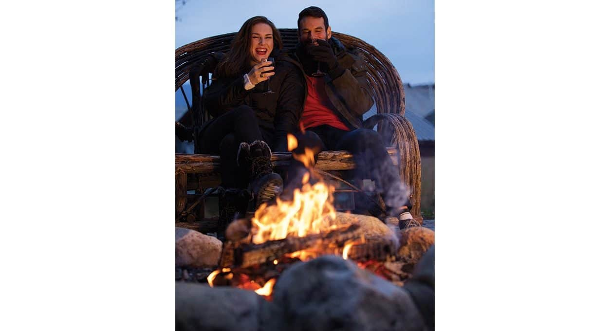 Couple enjoys a glass of wine near a fire at our hotel near mass moca