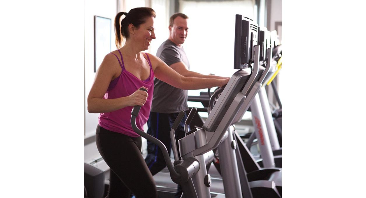 A woman and man working out on the treadmill and elliptical at the fitness center at Porches Inn.