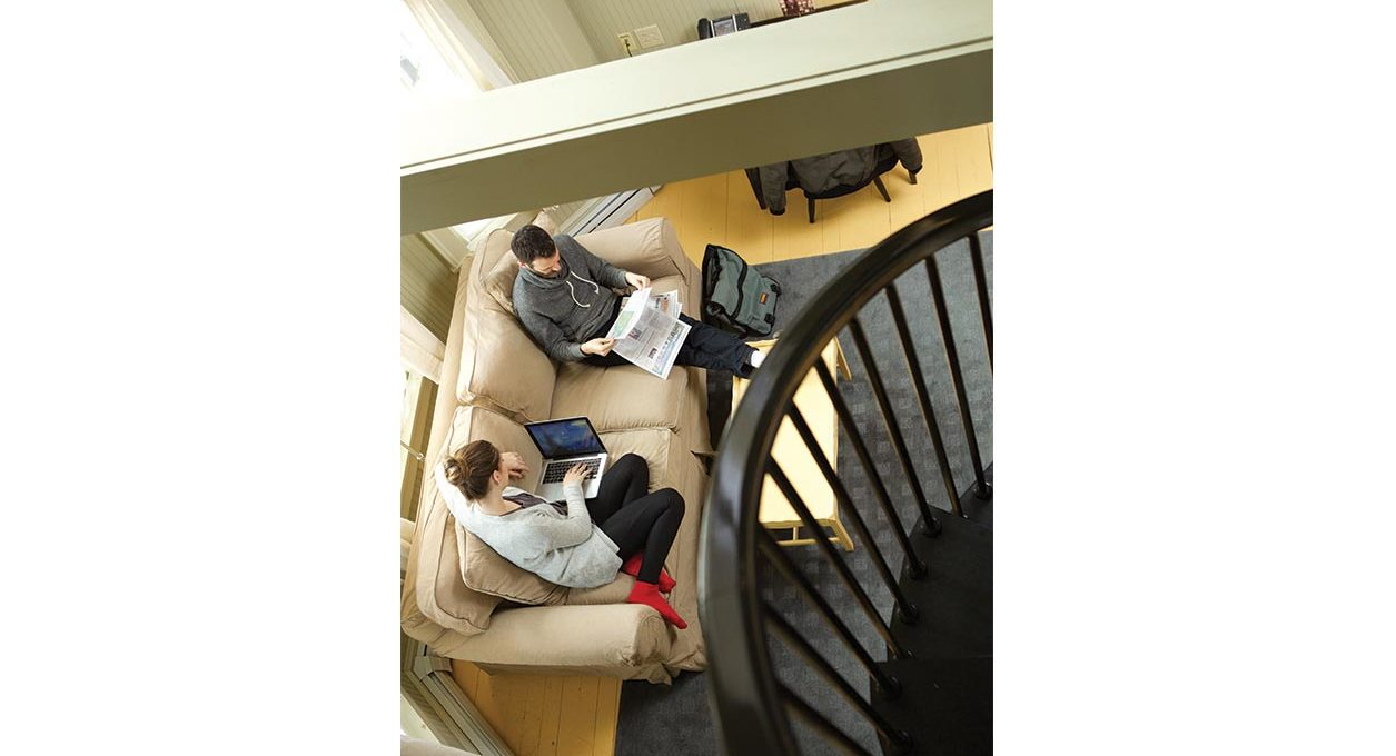 Bird's eye view of two people reading on a couch at our hotel in North Adams
